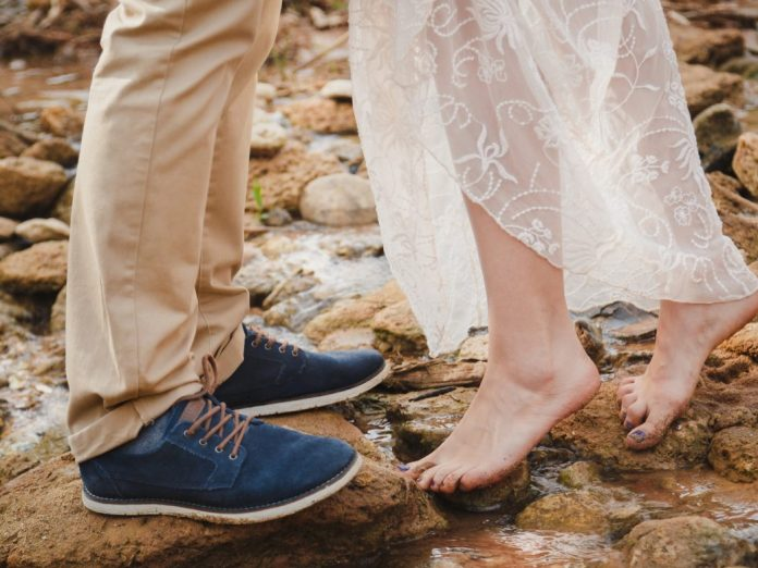 Close up of young woman feet standing barefoot on stones in front of mans feet wearing dark blue shoes- Best Places to Kiss in the Northwest