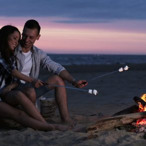 bonfire couple grilling smores on the beach