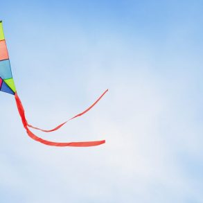 colorful kite flying with waving red bow from Cannon Beach Kite Shop
