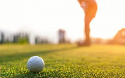Golfer woman putting golf ball on the green golf on sun set evening- Cannon Beach Golf Courses