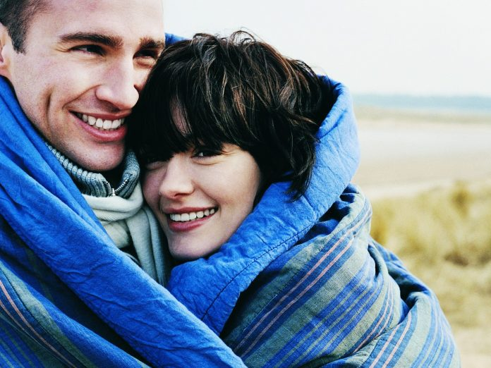 couple cuddling in a blanket at Arcadia Beach State Recreation Site