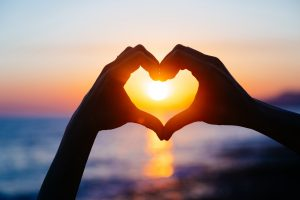 hands forming a heart shape with sunset silhouette. European romantic setting