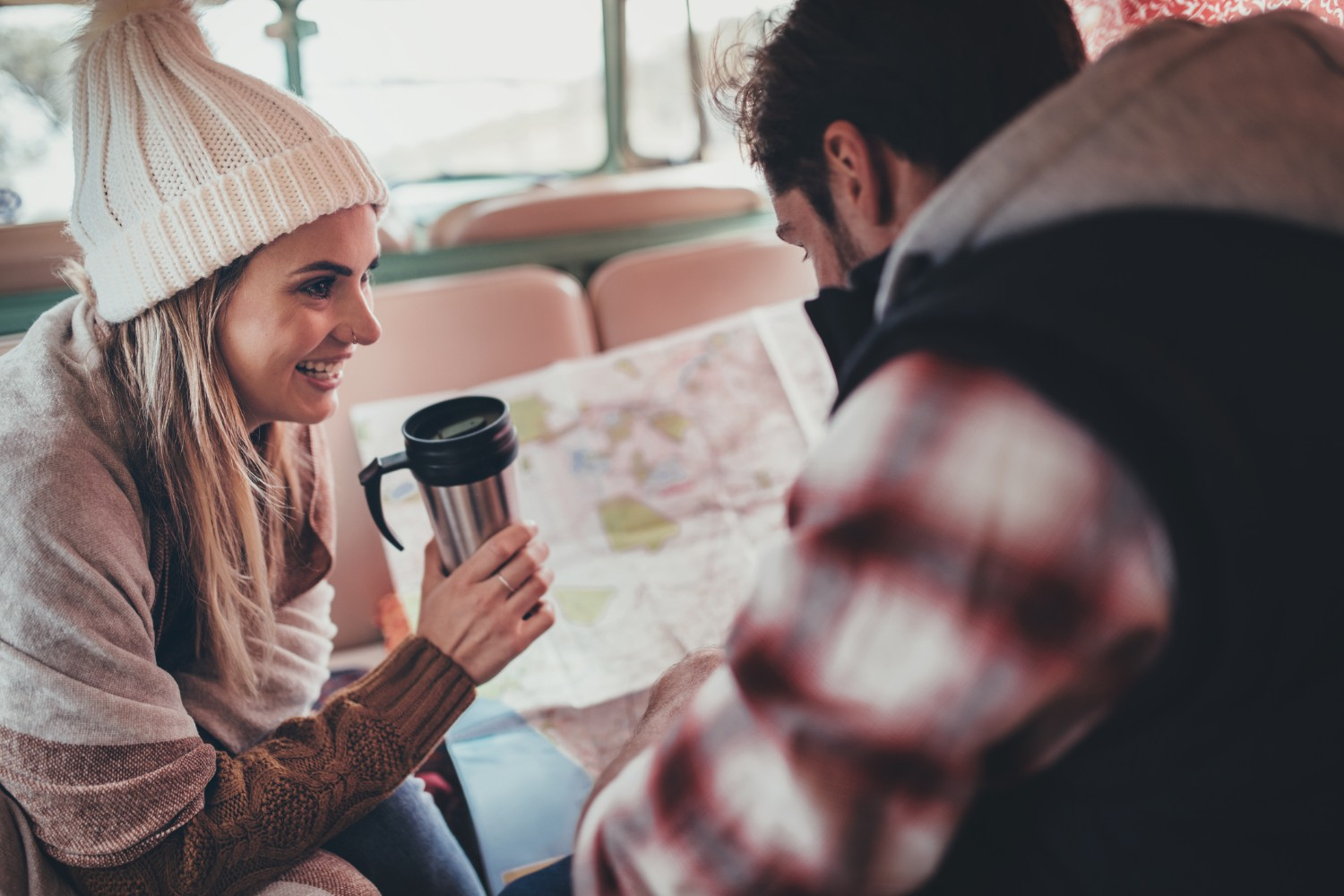 Couple planning a road trip with road map and thermos coffee