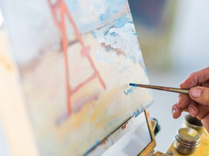 Cannon Beach Arts Association artist painting | close up of his hand and brush on the canva