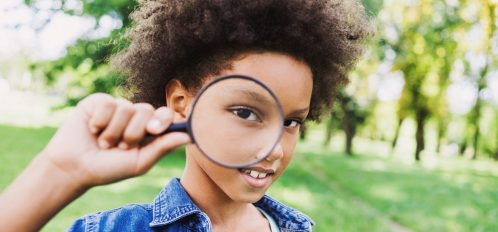 Beautiful african american little girl holding magnifying glass | Cannon Beach Escape Room Mystery Solving